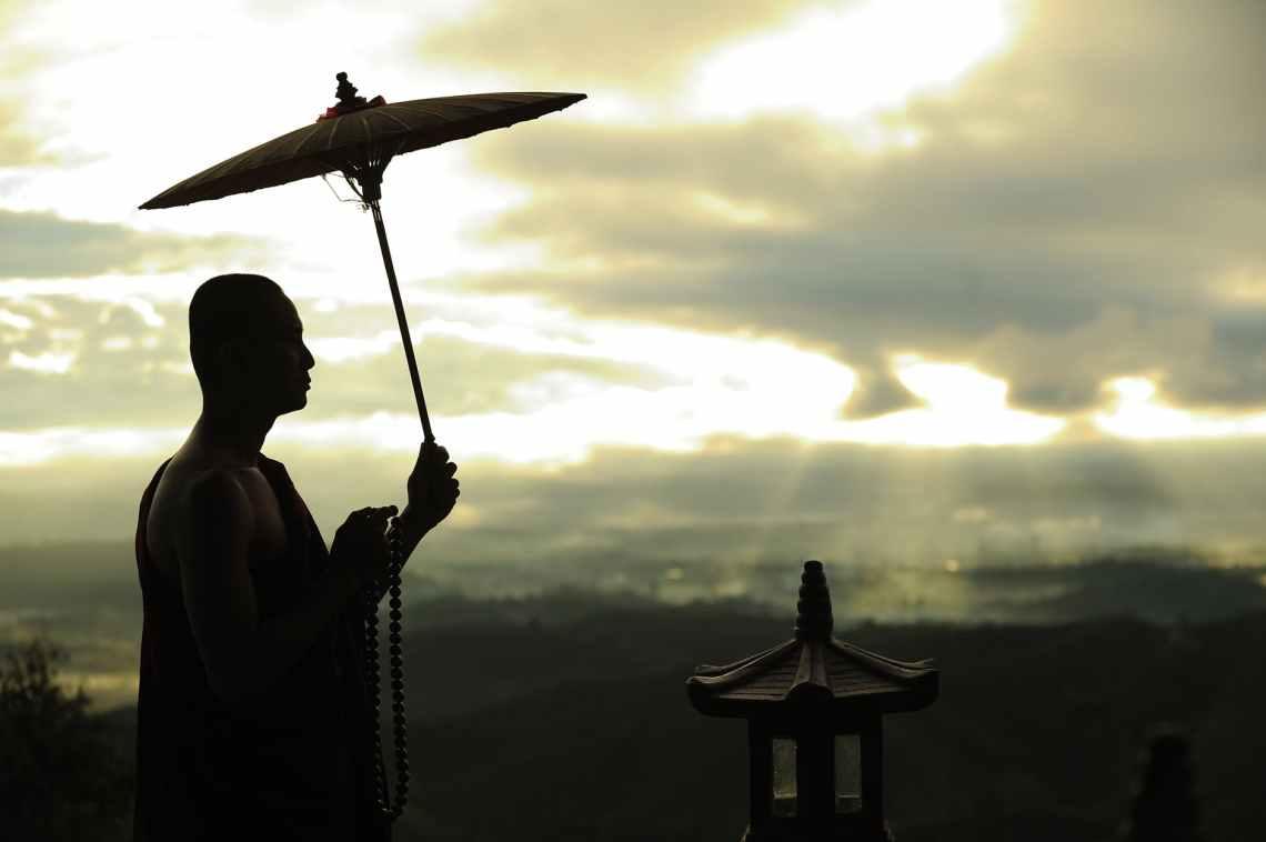 silhouette photo of monk holding umbrella